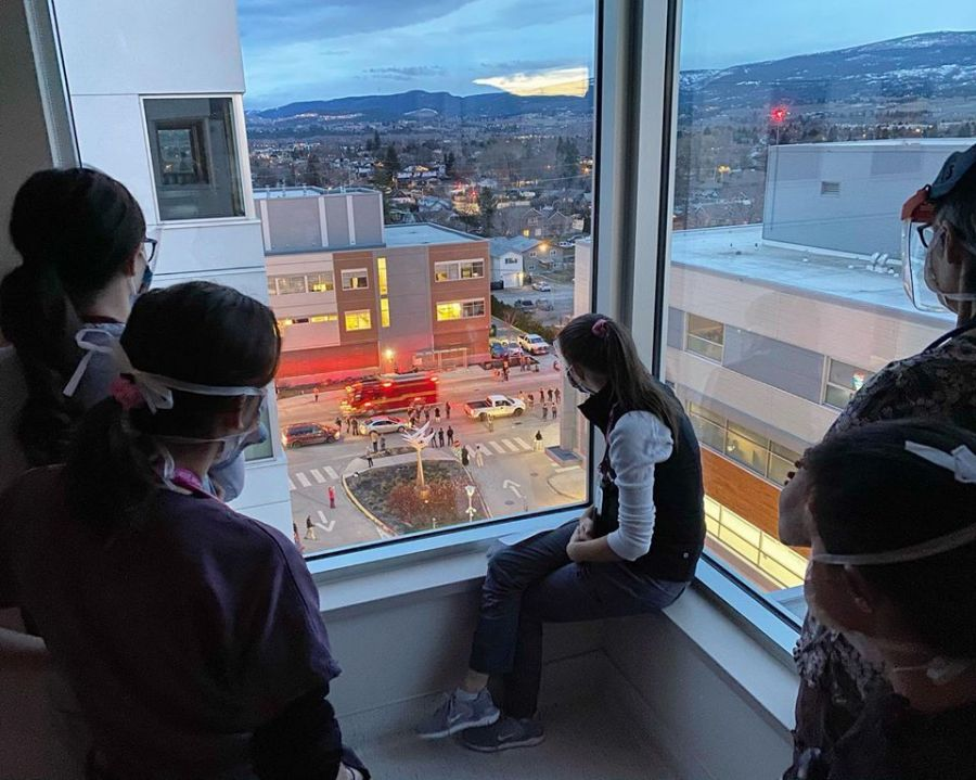 <who>Photo Credit: Amy Martens</who>Nurses inside Kelowna General Hospital's COVID-19 unit take a moment to watch Saturday night's procession of emergency vehicles in front of the hospital.